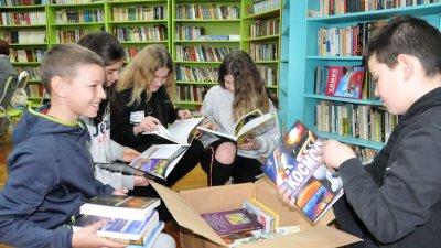 Възпитаници на СУ Св. св. Кирил и Методий разглеждат получените книги. Снимки Лина Главинова