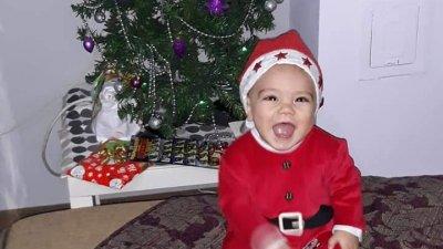 Иван е на 10 месеца и с усмивка позира пред елхата